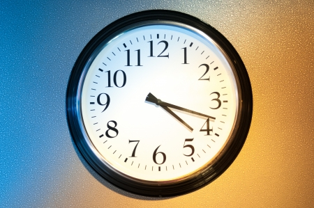 Black-and-white clock on wall with light and shade symbolizing day and night. Usual clock on two-coloured background: blue and light brown. Symbol of time passing away and future. photo