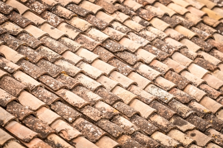 red clay: Close up detail of red clay roof tile with leaves and rainwater between rows in perspective view. Construction materials and house building. Abstract backgrounds and wallpapers. Stock Photo