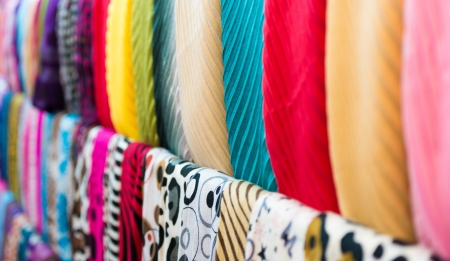 goffer: Close up view of colorful row of new scarves ready for sale at shop. Focus on blue and red ones. Going shopping and retail of casual clothes. Textiles and materials for sale. Trade and commerce. Stock Photo