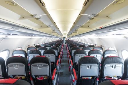boeing: Modern interior di aeromobili. Sedili neri e rossi dentro aeroplano. Simmetrico fila di fuga di posti a sedere all'interno del trasporto aereo. Classe di volo. Attrezzature per il viaggio. Piano illuminato vuoto.