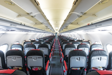 boeing: Modern interior of aircraft. Black and red seats inside airplane. Symmetric vanishing row of seats inside air transport. Economy class of flight. Equipment for travelling. Empty illuminated plane.