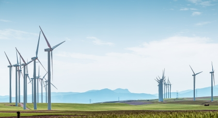 wind turbines: Rows of wind turbines on green boundless fields on background of blue cloudy sky and distant hills. Alternative energy source, production and power generation. Ecology and environment.