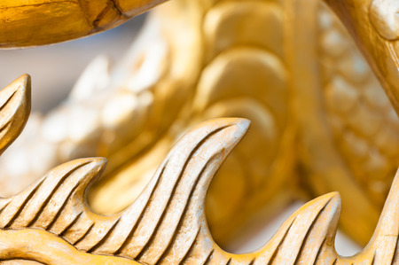 asian culture: Abstract image with focus on spine of dragon, symbol of asian culture. Golden sculpture showing part of animal. Wooden yellow painted statue. Traditional chinese art with fictional character.