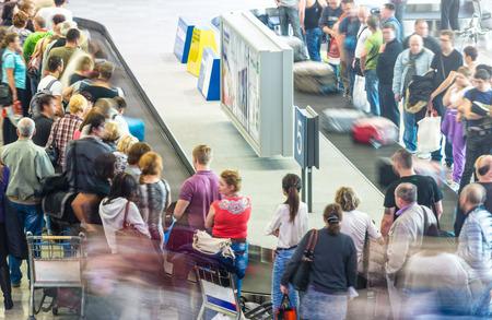많은 사람들이 비행 후 공항에서 컨베이어 벨트에서 수하물을 받고. 수하물 찾는 곳에서 수하물을 가져가는 승객 선. 항공 및 관광 여행.