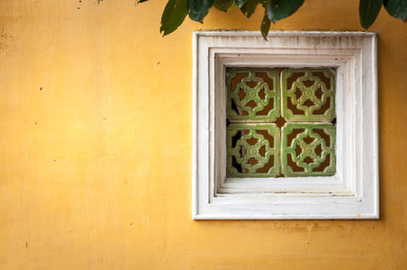 White wooden window with ornate green framing on wall of yellow stucco. Some green leaves over old worn window. House exterior in Vietnam, architecture of Asia. photo