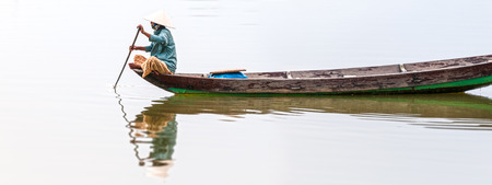 conical hat: Woman in conical hat sitting on canoe and rowing. Traditional asian boat made of wood. Person holding paddle in hands. Ripple on water. Reflection of vessel in river. Travel by boat in Vietnam, Asia.