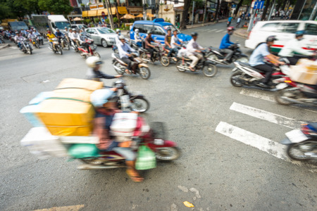 weighted: Motion view of street in Vietnam. Southeast Asia. Busy daily traffic with stream of motorbikes and cars. Blurry view of weighted scooter in foreground. Transportation and traffic.
