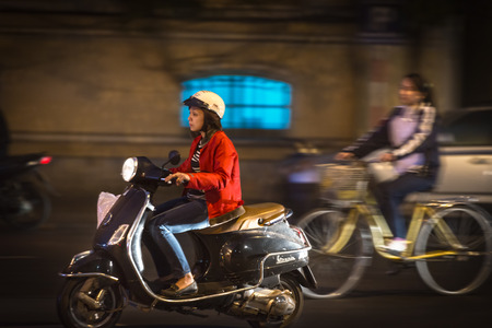 HANOI, VIETNAM - NOVEMBER 30: Woman in red jacket riding scooter at night. Most popular means of transport. Vietnam takes world 4th place in bike usage. November 30, 2012, Hanoi, Vietnam, Asia.