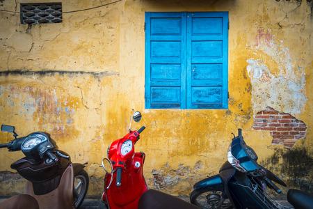 scooter: Fila de motos estacionados cerca del edificio de color amarillo con la pared sucia. Parking moto en la calle, Vietnam. Vida de la ciudad con el veh�culo c�modo y r�pido. Medio de transporte popular en los pa�ses asi�ticos. Foto de archivo