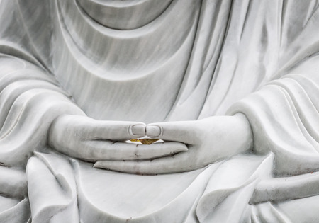 east asian culture: Marble statue of Buddha in close-up view with hands as main detail. Hands holding fragile leaf as symbol of peoples life. Art and culture of Asia. Religion and symbols of East. Stock Photo