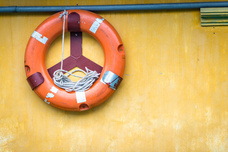 Yellow wall with orange buoy on it. Old lifebuoy with rope inside. Equipment for rescue of people. Precaution for survival in sea. Painted surface with pipe and ring-buoy. Service for lifesaving. Stock Photo