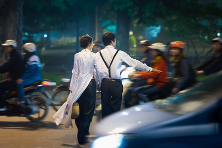 HANOI, VIETNAM - NOVEMBER, 30: Young couple crossing street. Chaotic traffic became everyday occurrence. About 20 thousand people die in accidents every year. November 3, 2012, Hanoi, Vietnam, Asia.