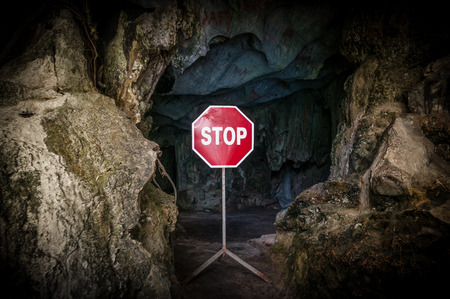 prohibitive: Entry to dangerous cave blocked with red and white Stop sign. Warning about danger on way to dark cave. Prohibitive sign at entrance to grot. Risky tourism and travelling. Stock Photo