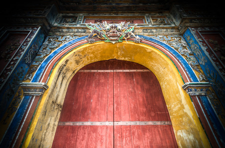 heritage protection: Beautiful wooden citadel gates in Hue city, Vietnam, Asia. Colored design of ancient building. Door with dragon face as symbol of protection. Famous destination for tourists. UNESCO Heritage site. Stock Photo