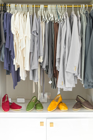 going for it: Row of new casual clothing on hangers at shop with four colorful pairs of shoes under it. Clothes presented as in wardrobe. Apparel ready for sale. Going shopping. Trade and commerce.