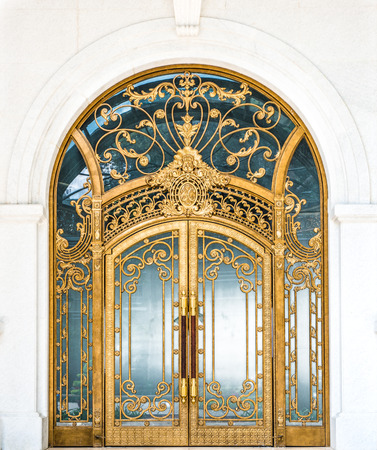 arch: Beautiful arched doorway. Door made of wood, gold and glass reflecting arch. White wall of building with elegant gilded entrance. Old style of door with golden ornate details. Tourist attraction.