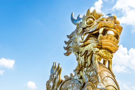 religious culture: Golden stone dragon statue in Vietnam with face close-up on blue sky background. Leftside view. Symbol of vietnamese mythology and folklore. Religion, culture and art of Asia.