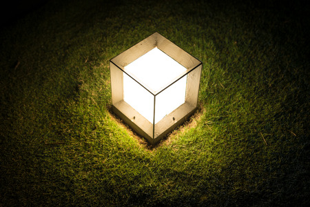 garden lamp: Garden lantern in shape of cube with dim light striking upon green lawn at night. Outdoor decoration and lighting. Warm and romantic atmosphere of evening. Illumination in garden or park. Stock Photo