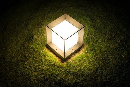 Linterna de jardín en forma de cubo con luz tenue llamativa sobre césped verde en la noche. La decoración y la iluminación al aire libre. Un ambiente cálido y romántico de la noche. Iluminación en el jardín o parque.