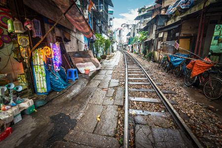 risky: Perspective view of railway running along narrow street with houses in Hanoi, Vietnam. Unusual solution of transport problem. Dangerous neighborhood for people. Travelling and tourism.