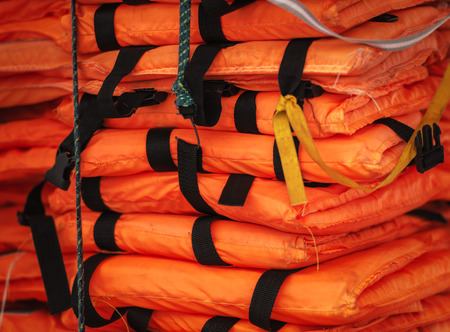 flotation: Close-up view of packed orange life-jackets pile ready for shipping. String with hook holding jacket. Safety control on board ship. Sea travelling. Stock Photo
