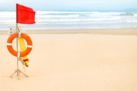 safety device: Life saving devices hanging on wooden rack with red flag and warning table no life-guard on duty on empty beach. Ocean and blue sky in background. Safety and caution measures during swimming. Stock Photo