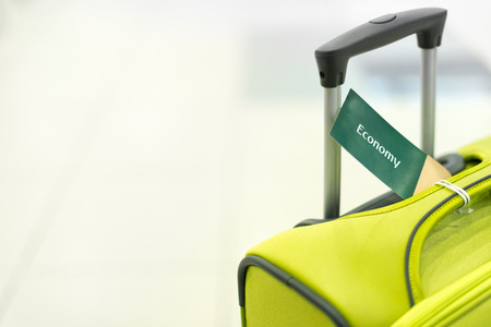 Bright suitcase with handle and label economy. Luggage at airport. Modern and elegant bag for travel. Object on white background. Tag with information on baggage. Bag for tourism and vacation. photo