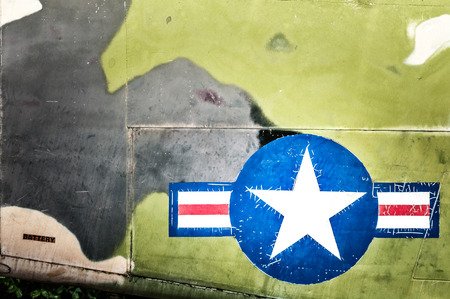aside: Part of military airplane with United States Air Force sign. Big white star in blue circle with stripes aside. War aircraft in metal plates. Military aviation. Retro style. Safety and protection. Stock Photo
