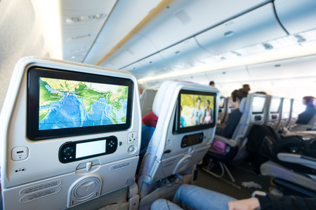 Cabin with people aboard looking at LCD monitors. Colorful flight map and film on screens. Passenger plane interior. Fast and comfortable travelling. Monitor as means of getting fun and information.