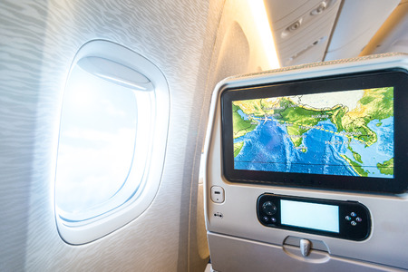 Back of seat with LCD monitor. Window with sunlight and cloudy sky can be seen next to it. Colorful map of flight on screen. Passenger plane interior. Fast and comfortable way of travelling.