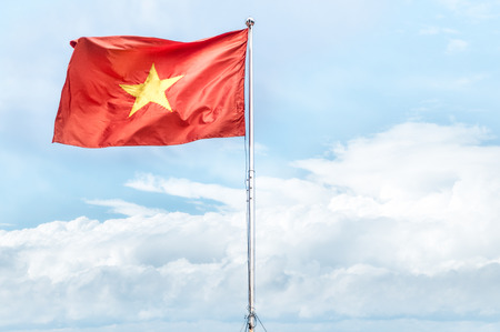 vietnam flag: Metal pole with waving banner. Red flag with yellow star, blue sky with clouds in background. Rippled texture. National flag of Vietnam. Popular country for tourism. Famous tourist destination.