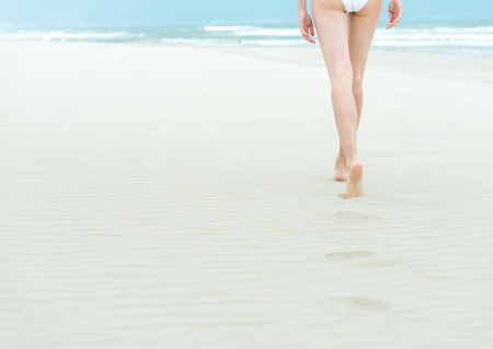 gentle dream vacation: Young slim woman in white swimsuit walking to sea or ocean leaving footprints on soft sand. Blue ocean waves with foam in background. Bathing or sunbathing on beach. Holidays and vacations in summer.