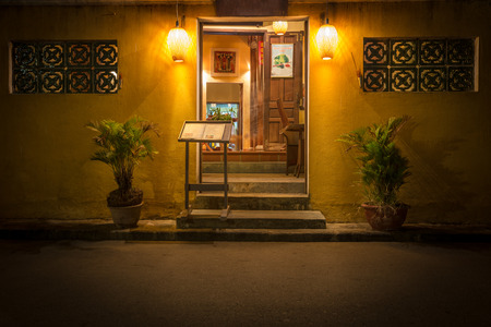 restaurant exterior: Open door to old cafe in Hoi An. Restaurant at night in Vietnam, Asia. Stand with menu at entrance. Plants in pots. Light from lamps. Traditional asian place to eat. Beautiful design of windows. Editorial