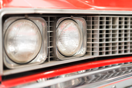 shiny car: Close Up Detail of Headlight of Shiny Red Classic Car Stock Photo