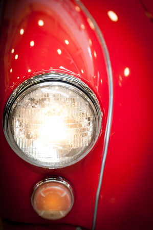 lens unit: Close Up Detail of Headlight of Shiny Red Classic Car Stock Photo