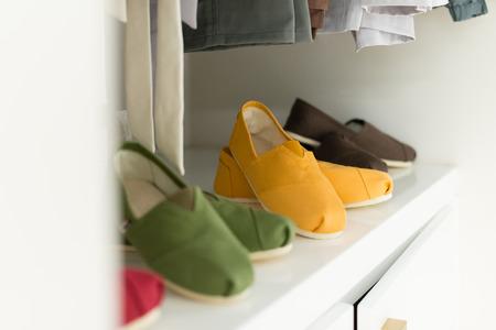 tienda zapatos: Fila de nuevas ropa casual en perchas en la tienda con cuatro pares de colores de zapatos debajo de ella. Ropa presentan como vestidor. Ropa listo para la venta. El ir de compras. Comercios.