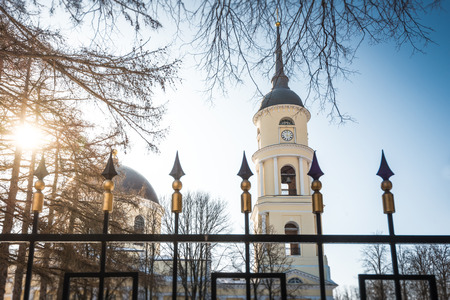 View of dome and bell tower of Orthodox Church through bars of fence. Winter sunny day, blue sky. Bell tower and church of pale yellow color with white details. photo