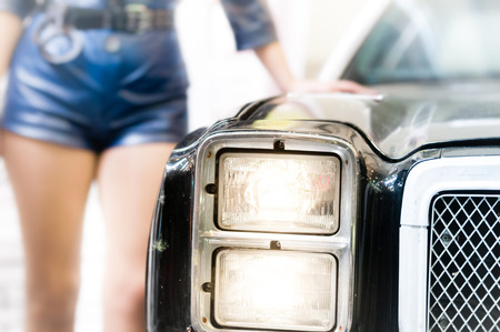 Women dressed like police officer leans her elbow on old, rare and stylish model of police car. She is wearing shorts. There are handcuffs on her belt. photo