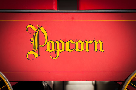 Vintage Style Yellow Popcorn Print Isolated on Red Background. photo