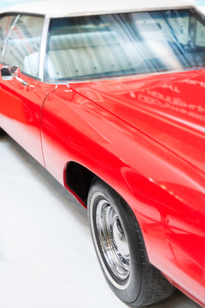 coachwork: Close Up Detail of Shiny Red Classic Car in Studio with Focus on Wheel, Hood, and Windshield. Stock Photo
