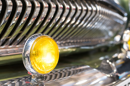 grille: Round yellow head light of retro automobile. In background, shiny chrome radiator grille of vehicle, with reflection. Background slightly blurred.