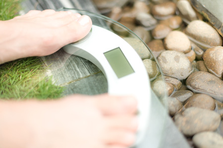 excess weight: Person on scale with only feet to be seen on green lawn and wet pebble background. Person measures weight in spa setting. Health care and weight loss. Spa helps to be fit.