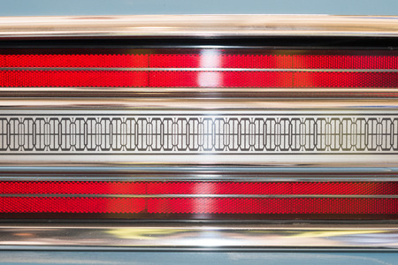 taillight: Car taillight. Blue white red black-brown symmetrical pattern with brown lines. Glare noticeable. Old or retro car light details. Stock Photo