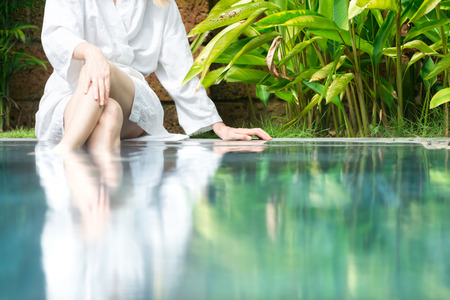 Slim woman in white bathrobe sitting at pool in hotel with her feet in blue clear water. Fresh and natural atmosphere with green plants around. Hotels and resorts. Spa procedures and healthcare. Stock Photo