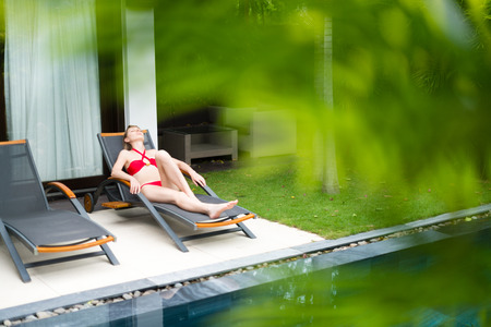 chaise longue: Young woman in red swimsuit relaxing on chaise longue near pool. Blurred palm tree leaves in foreground. Comfortable sunbathing in hotel area. Summer vacation on tropical resort. Stock Photo