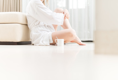 Woman in white bathrobe sitting on floor in hotel room. Beautiful and elegant interior. Bedroom in soft colors. Cup of coffee next to girl. Person relaxing and drinking tea. photo
