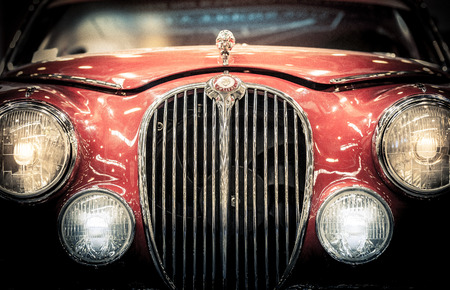 Moscow, Russia - March 3, 2013: Front headlights and grille of a restored red vintage Jaguar motor car showing the badge and hood ornament, close up frontal. Editorial