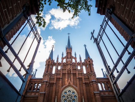 catholicity: Open metallic gate towards an old Christian church with impressive architecture, under a cloudy blue sky, concept of salvation, heaven and spiritual comfort, from low-angle.