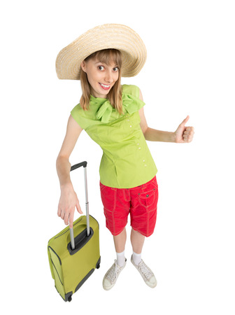 somebody: Happy lady tourist in red shorts and green blouse with big suitcase to travel. Isolated on white background. Interesting trip on summer vacation. Woman greeting to somebody.