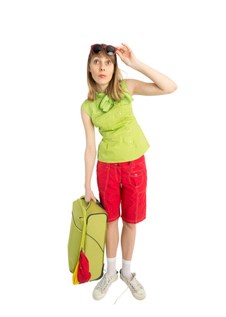 Happy lady tourist in red shorts green blouse and sunglass with big suitcase to travel. Isolated on white background. Interesting trip on summer vacation. Bag not close. Woman looking for hotel. photo